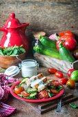 Salad with fried chicken, zucchini, tomatoes and yogurt dressing