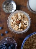 Granola in an antique jar, wild blueberries in a glass jar and granola in a bowl