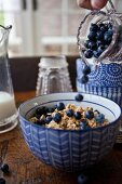 A woman pouring wild blueberries from a jar onto a bowl of granola with milk