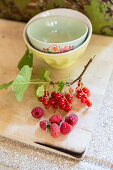 Sprig of redcurrants and raspberries on wooden board