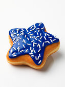 A star-shaped doughnut with blue glazing and white hundreds and thousands