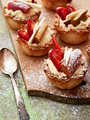 Rhubarb, strawberry and coconut tartlets on a wooden board
