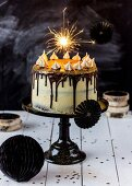 A brownie cheesecake decorated with a sparkler on the top