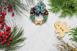 Christmas cookies on wooden table with Christmas decorations and decorated straw wreath