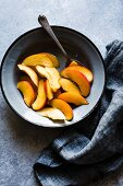 Peach wedges and a spoon in an enamel dish