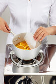 Chef removes baking paper from a suace pan filled with orange slices
