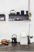 Teapot on concrete worksurface below wall-mounted shelves and pendant lamp in kitchen