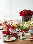 A table laid with crayfish, croissants, apple tart, mayonnaise, and horseradish schnapps (Sweden)