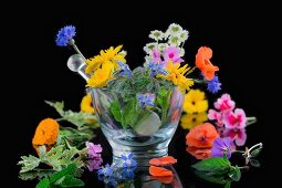 Various healing flowers in a glass mortar
