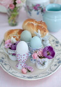 Eggs in egg cups, flowers in cups and pastries on Easter table