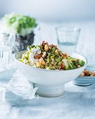 Spicy bulgur salad with sprouts, celery, apple, herb dressing and honey almonds