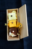 Petit fours with gold foil in a wooden box
