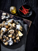 An arrangement of ingredients with fresh clams on ice, chilli and olive oil