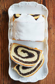 Poppy seed cake with icing and two slices cut off
