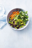 Black rice salad with edamame beans, gherkins, carrots and corriander