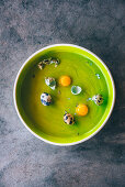Whole and cracked quail eggs in a green bowl