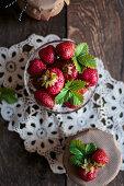 Fresh strawberries in a glass between two jam jars
