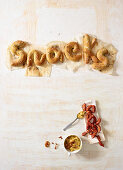 The word 'snacks' made from salted bread with mini sausages with mustard
