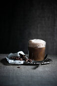 Iced coffee with foamed chocolate soya drink served with dark chocolate and popped oats