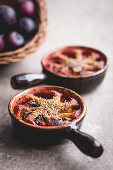 Dairy free plum clafoutis on a stone background and plums, autumn style