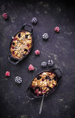 Clafoutis with raspberries, blackberries, flaked almonds, icing sugar and a fork