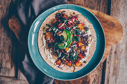 A wholemeal wrap with flower sprouts, roasted vegetables, tahini and mustard dressing and pomegranate seeds
