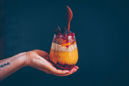 A hand holding a glass of parfait