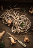 Raw chanterelle pasta, with fresh chanterelles, parsley and a knife on a wooden background
