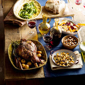 A table laid with a roasted leg of lamb, mushrooms, vegetables and wine