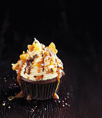 A chocolate cupcake with peanut butter and caramel sauce