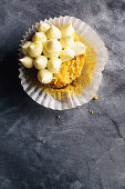 A pumpkin and walnut cupcake with a bite taken out