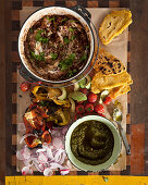 Grilled pork shoulder with black beans, chimichurri and pupusas