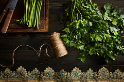 Fresh cilantro leaves with a spool of thread