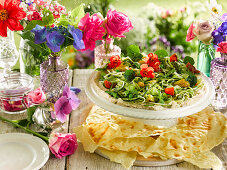 Summer salad with edible flowers, hummus and flatbread