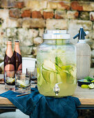 Cold ginger beer and gin punch with cucumber and lime in a drink dispenser