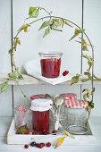 Cornelian jam in storage jars under a cornel cherry branch