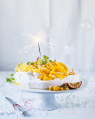Pavlova with exotic fruits and a sparkler