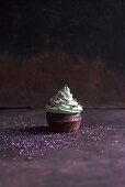 A chocolate cupcake with pistachio cream, sugar stars and edible glitter (vegan)