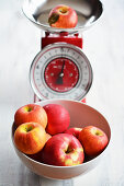 A bowl of red apples and one on an old-fashioned pair of kitchen scales
