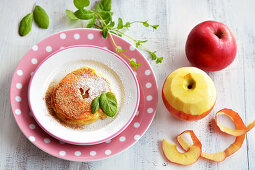 Battered apple rings on a plate with cinnamon, sugar and mint