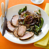 Sliced pork tenderloin with onions and greens