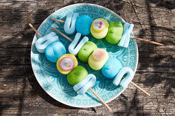 Sweet marshmallow skewers on wooden table outside