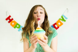 A young woman blowing out the candle on a birthday muffin