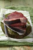 Three slices of raw tuna on a chopping board