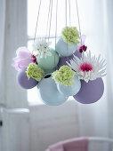 Easter arrangement of flowers in suspended spherical vases