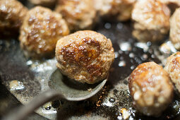 Meatballs being fried in a pan