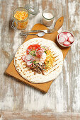 A tortilla topped with pork, coleslaw and vegetables