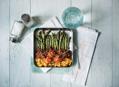 Green asparagus with red quinoa, lentils and baked tomatoes