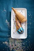 Blue vegan ice cream with chocolate sauce and sugar confetti in cones