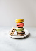 A stack of colourful macarons against a white background